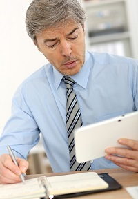 Senior business owner with a tablet computer preparing short-list of prospective buyers of his company
